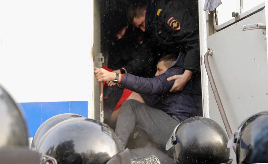Митинг в поддержку политика Алексея Навального и шествие от Дома офицеров к площади Ленина. Сотрудники полиции во время задержания и посадки в автозак участника митинга