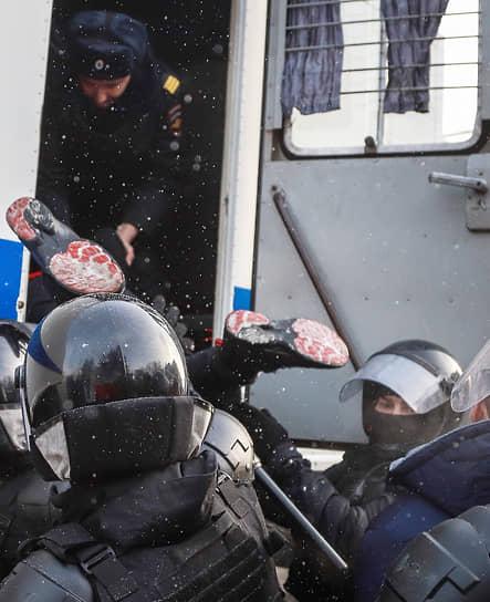 Сотрудники полиции во время задержания участника акции в поддержку политика Алексея  Навального