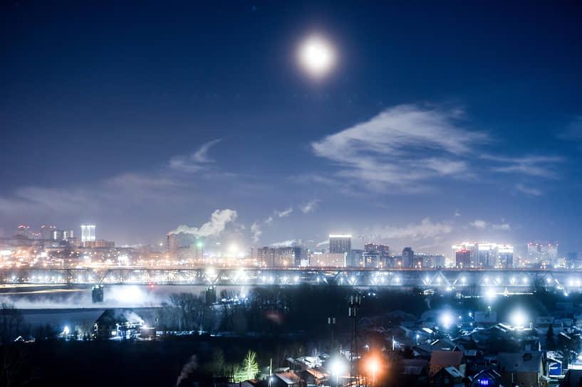 Железнодорожный мост через реку Обь в Новосибирске на фоне жилых домов на правом берегу в ночное время