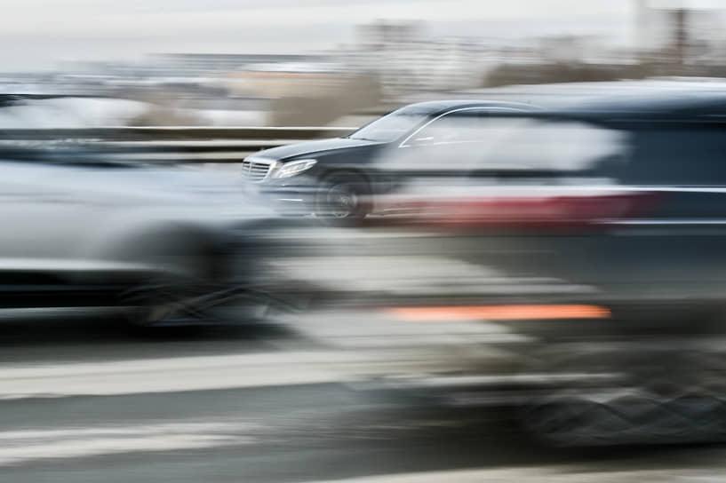 Городской трафик. Автомобиль Mercedes едет с большой скоростью по Дмитровскому мосту в Новосибирске
