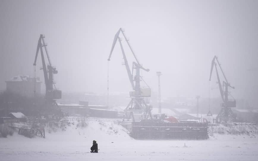 Рыбак на льду реки Обь в Новосибирске на фоне портовых кранов