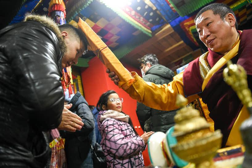 После завершения ритуала прихожане покидают храм, проходя мимо ламы (лама — настоятель храма), который благословляет верующих священным текстом, который завернут в ткань