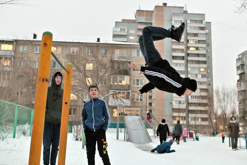 Молодые люди занимаются силовыми упражнениями на турнике во дворе жилого дома