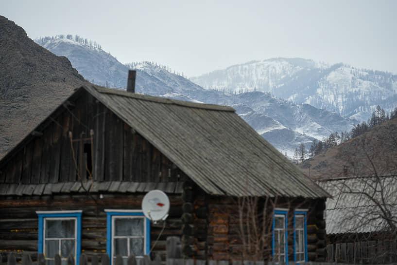 Зимние виды Республики Алтай. Старый деревенский дом близ села Онгудай на фоне гор Алтая