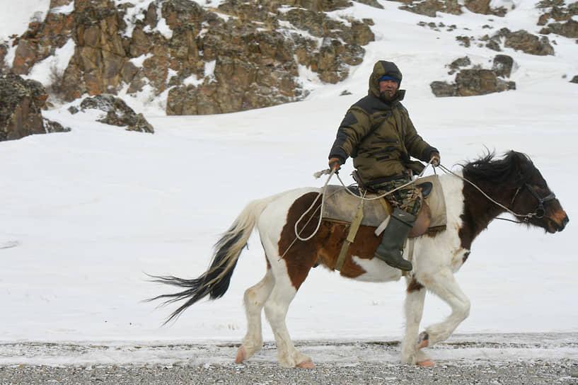 Алтаец едет на лошади в горах