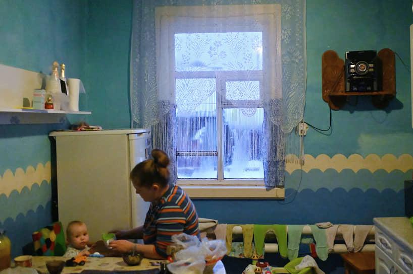 Жизнь и быт в отдаленных поселениях Сибирского федерального округа. Деревня Литовка Омской области. Мама кормит ребенка