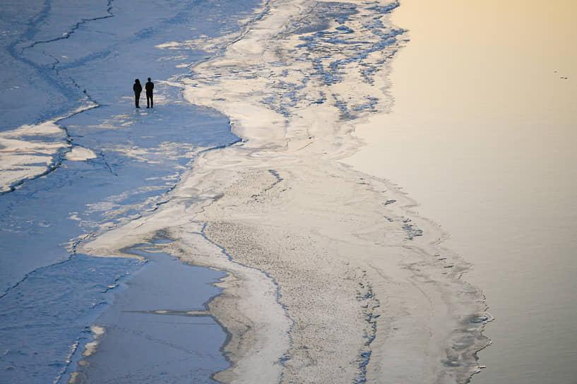 Начало весеннего ледохода на Оби. Люди гуляют на краю льдины во время заката