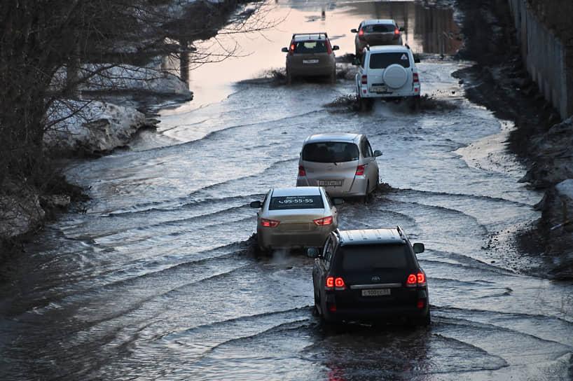 Виды Омска во время весенней распутицы.  Автомобили едут по затопленной дороге