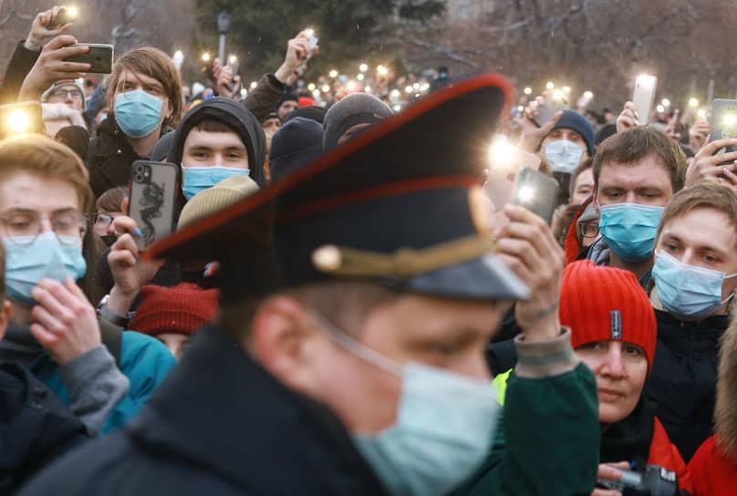 Несанкционированный митинг в поддержку оппозиционера Алексея Навального. Сотрудник полиции и участники акции с включенными фонариками на мобильных телефонах