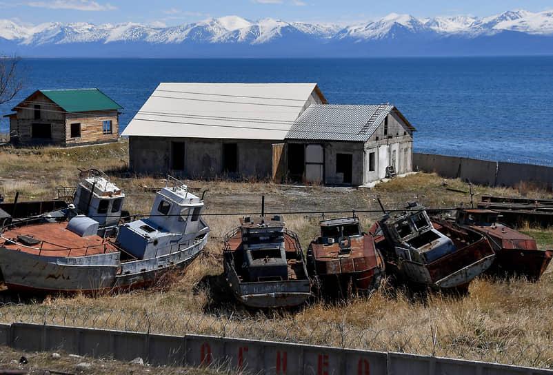 Заброшенный дом и старые катера на берегу озера Байкал в Нижнеангарске