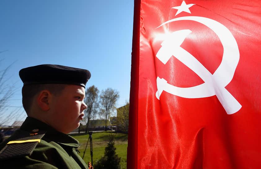 Празднование Дня Победы в поселке Евсино Искитимского района. Юноша в военной форме у Флага СССР