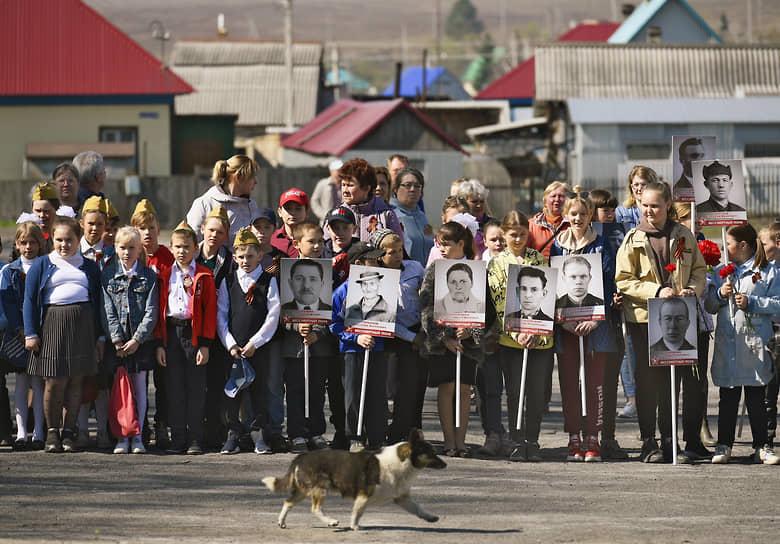 Празднование Дня Победы в селе Листвянское Искитимского района. Дети с фотографиями односельчан — героев войны в рамках акции «Бессмертный полк»