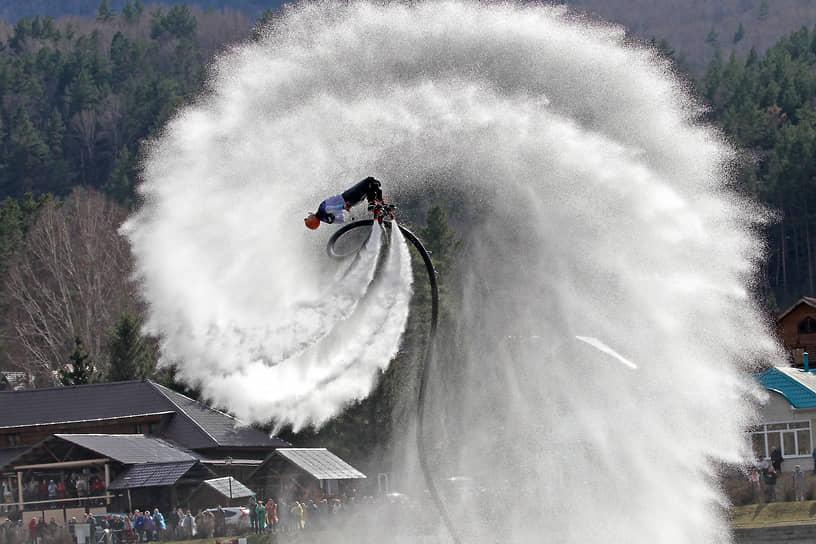 Флайборд шоу на открытии летнего туристического сезона на Алтае. Спортсмен на флайборде во время празднования на фоне алтайских гор