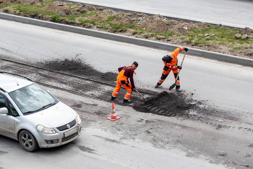 Сотрудники дорожных служб ремонтируют дорожное покрытие на Ипподромском шоссе в Новосибирске