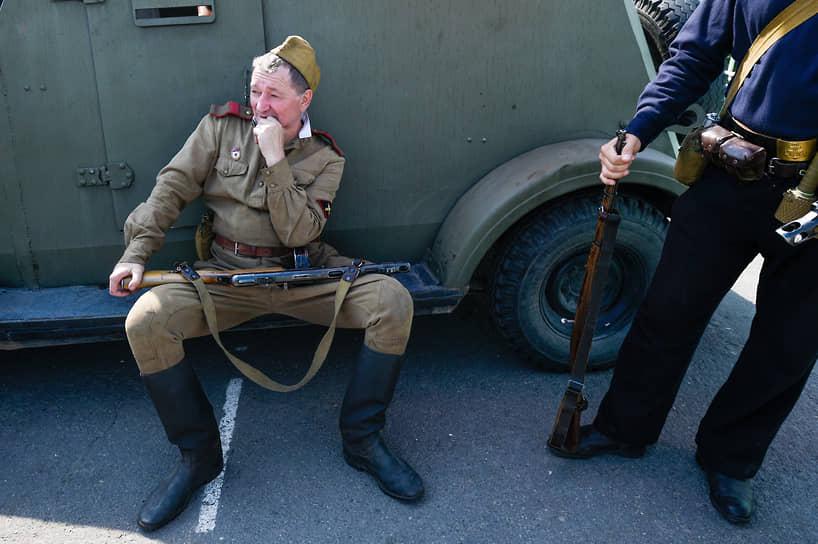 Церемония встречи агитационного поезда Министерства обороны России «Мы — армия страны, мы — армия народа», на железнодорожном вокзале Новосибирск-Главный в Новосибирске. Мужчина-реконструктор сидит с ППШ у военного броневика