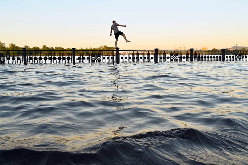 Молодой человек стоит на ограждениях на затопленной набережной реки Енисей в центре города. Из-за больших запасов снега в горах Саяны в этом году был экстремальный паводок на Енисее, возможно, сильнейший за 100 лет