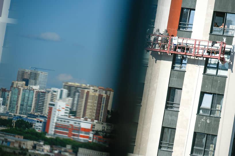 Промышленные альпинисты во время покраски фасада здания в Новосибирске