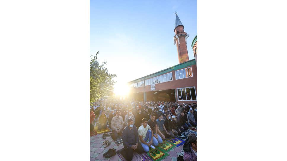 Праздник жертвоприношения Курбан-Байрам на территории Новосибирской Соборной мечети. Верующие во время намаза возле мечети в лучах рассветного солнца