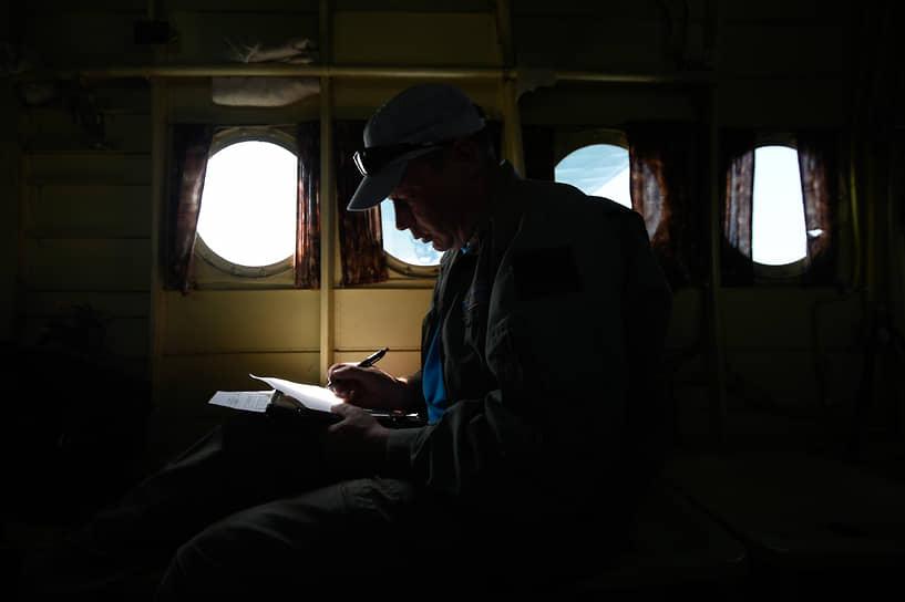 Сотрудник Новосибирской авиабазы на борту самолета, выполняющего полет по обнаружению лесных пожаров