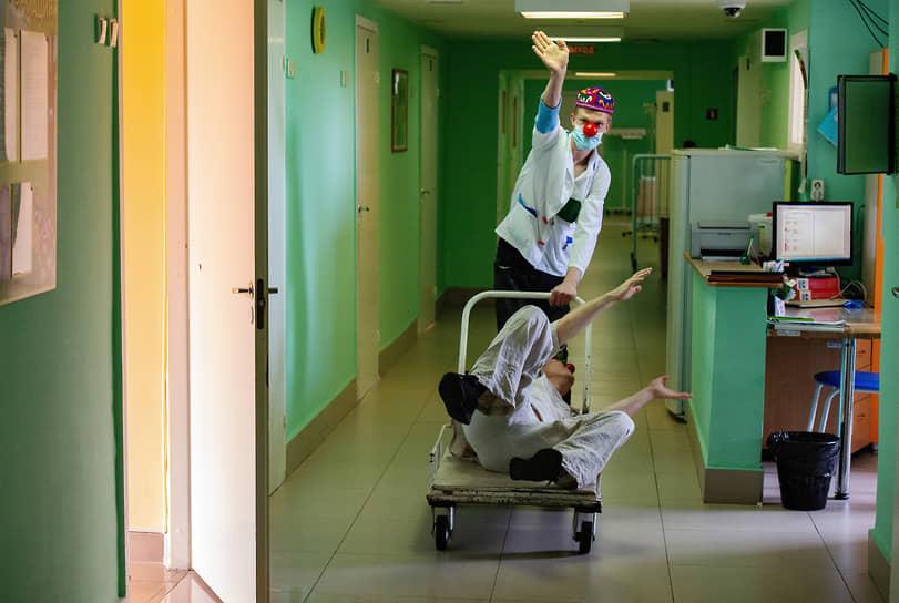 Больничные клоуны — это волонтеры, специально отобранные и прошедшие обучение в школе больничной клоунады, они регулярно приходят к детям, находящимся на стационарном лечении в медучреждениях. На фото: клоуны Тумаша Советский и Дылда во время посещения инфекционного отделения Детской городской клинической больницы №3