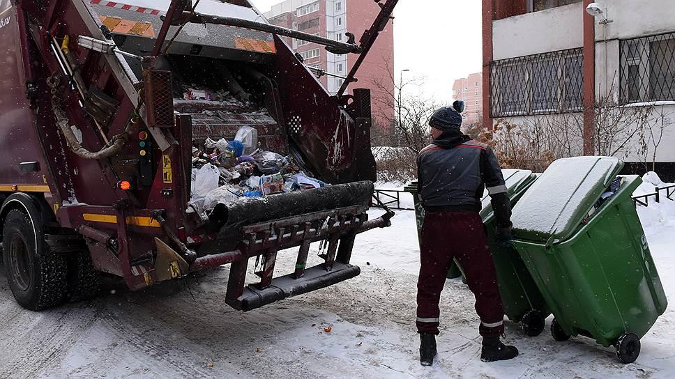 Сотрудник компании по вывозу мусора во время загрузки контейнеров с отходами