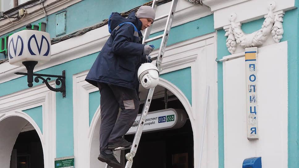Специалист по установке приборов уличного видеонаблюдения перед монтажом камеры на доме в центре Санкт-Петербурга