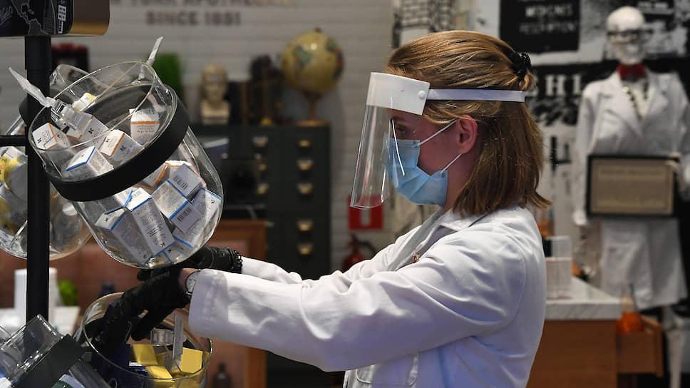 Продавщица парфюмерного магазина в маске и защитном экране
