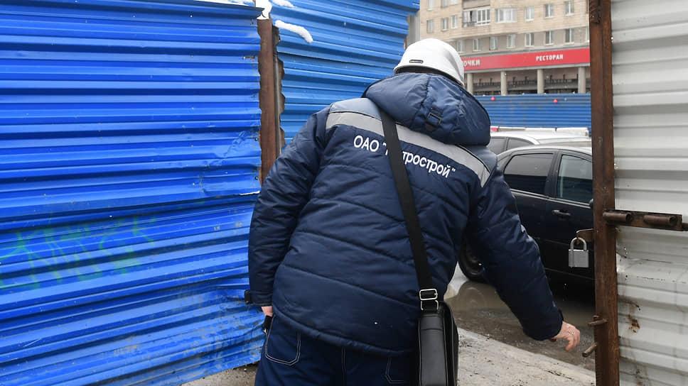 """Сотрудник компании """"Метрострой"""" закрывает ворота на строительную площадку"""