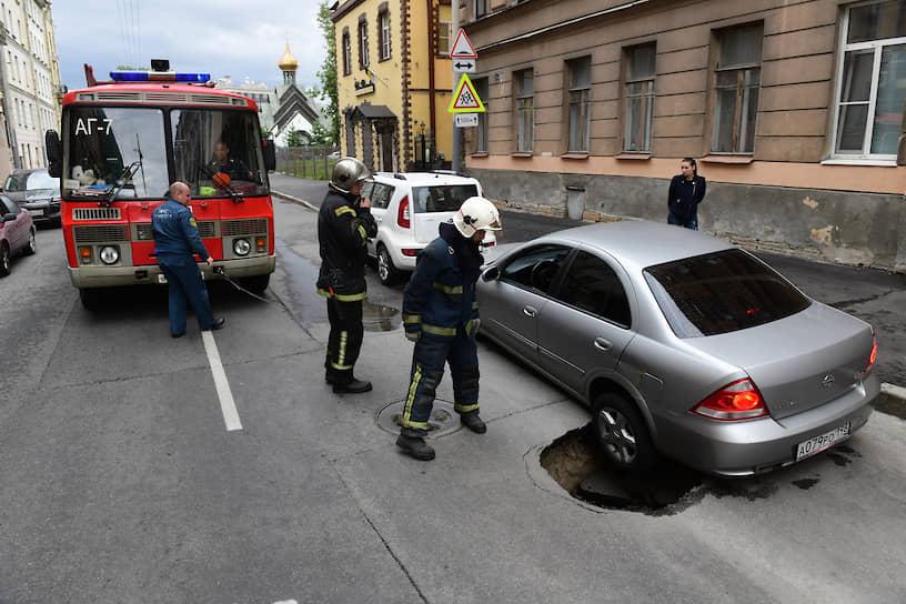 Сотрудники МЧС осматривают провал грунта под автомобилем в центре города