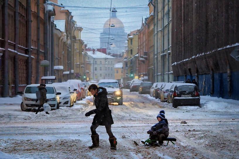 Женщина с ребенком пересекает занесенную снегом проезжую часть в центре города во время снегопада
