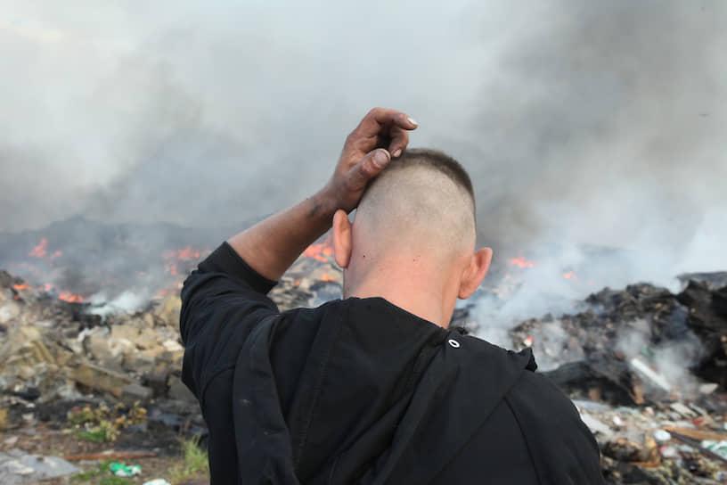 Мужчина смотрит на горящую несанкционированную свалку на окраине Санкт-Петербурга