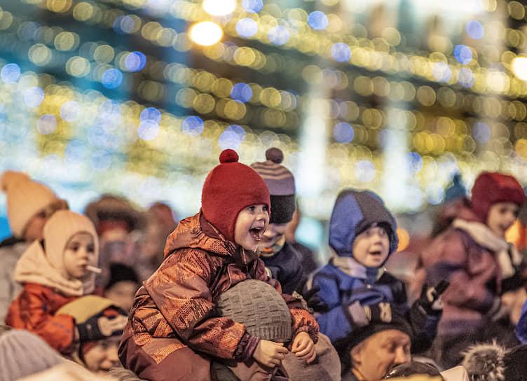 Дети смотрят на выступление Деда Мороза из Великого Устюга на Манежной площади