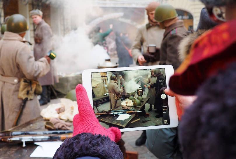 Участница акции снимает на айпад (iPad) реконструкцию военных лет