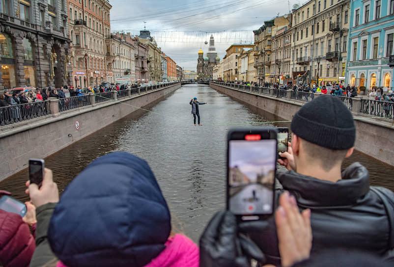 Мужчина-канатоходец идет по канату через канал Грибоедова