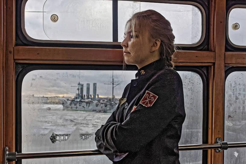 """Девушка в стилизованной форме кондуктора в экскурсионном ретротрамвае во время следования мимо крейсера """"Аврора"""""""