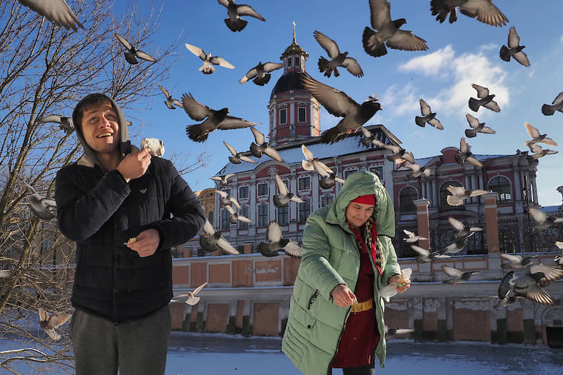 Люди кормят голубей у Александро-Невской Лавры