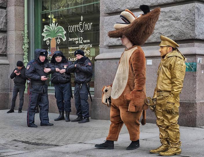 Актеры развлекающие туристов в центре города на фоне сотрудников полиции