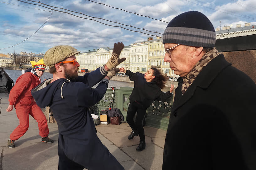 Мужчина идет мимо любителей уличных танцев на Аничковом мосту
