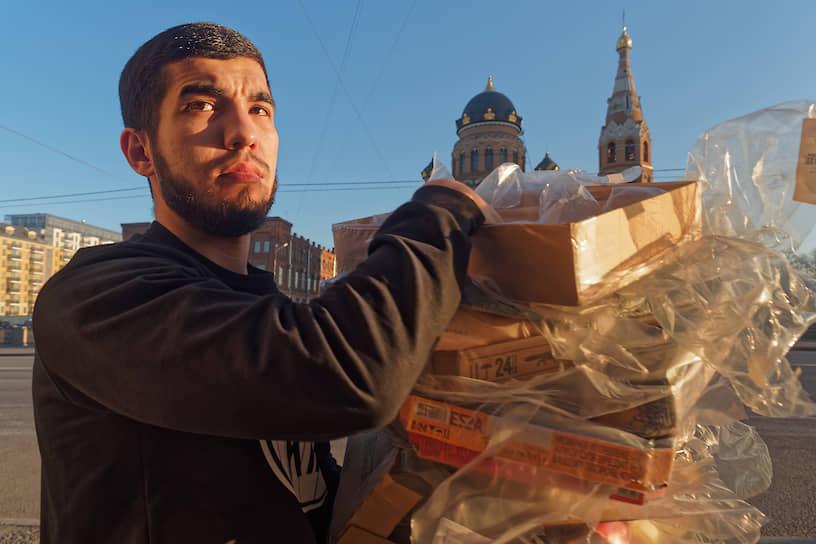 Мужчина несет использованные продуктовые упаковки на фоне православного собора