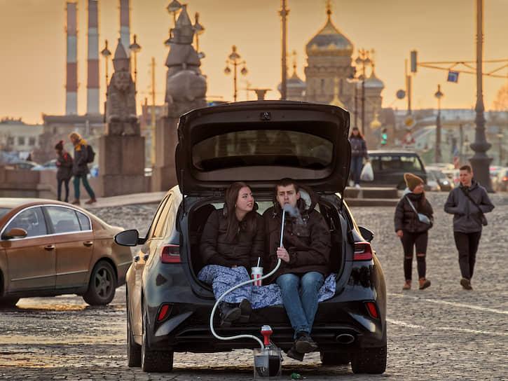Молодые люди сидят в багажнике автомобиля на набережной Невы
