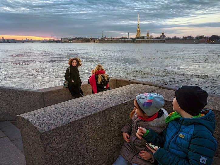 Отдыхающие на набережной Невы напротив Петропавловского собора