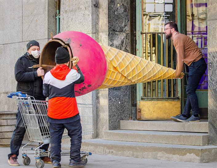 Люди в медицинских масках заносят рекламный стенд в форме мороженого в рожке в здание кафе