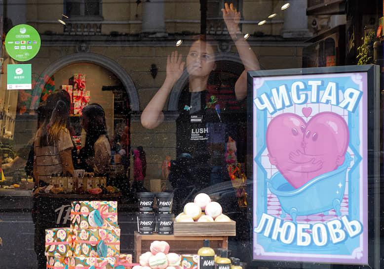Продавщица в витрине косметического магазина