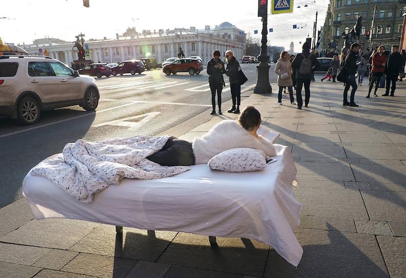 Девушка лежит в постели на Невском проспекте и читает книгу, призывая к добровольной самоизоляции из-за пандемии коронавируса COVID-19