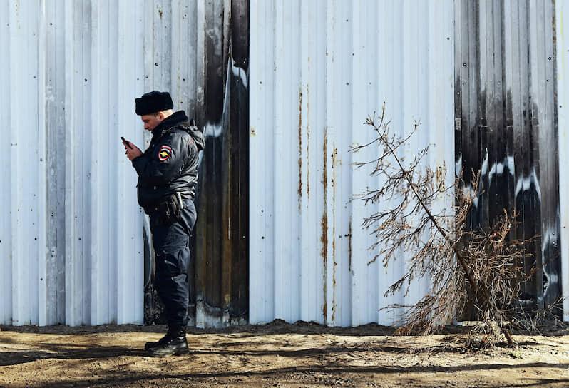 Полицейский с мобильным телефоном у забора, закрывающего несанкционированную свалку
