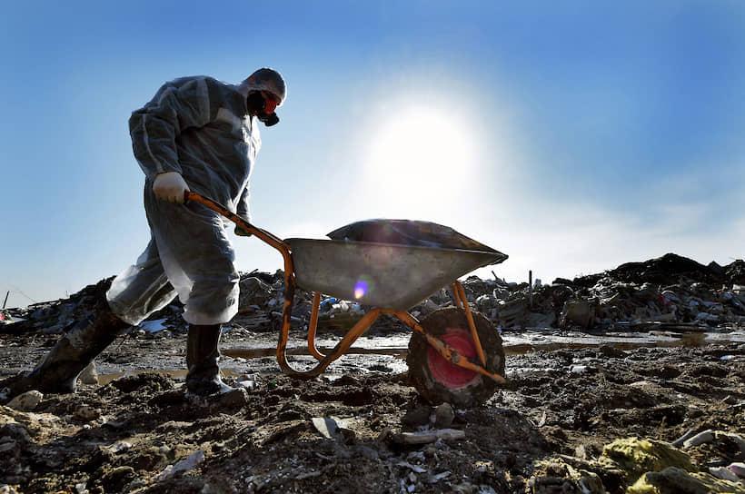 """Сотрудник компании ГУП """"Экострой"""" во время работ по утилизации опасных отходов и мусора на несанкционированной свалке во Всеволожском районе Ленинградской области"""