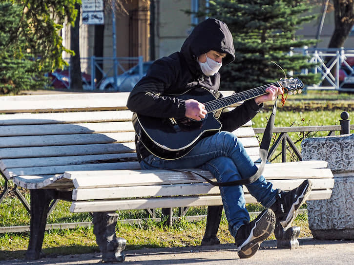 Мужчина в медицинской маске играет на гитаре в сквере города Колпино