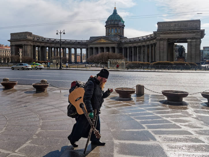 Служитель церкви с гитарой идет по пустому Невскому проспекту на фоне Казанского собора