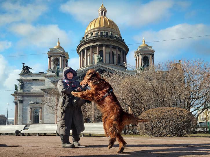 Женщина выгуливает собаку возле Исаакиевского собора