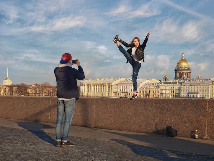 Молодые люди фотографируются на набережной